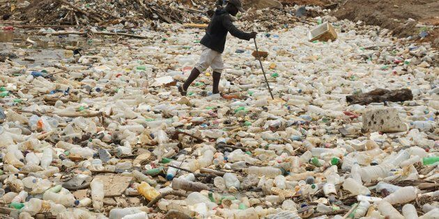 A man walks between plastics bottles in a river near Abidjan in Ivory Coast on May 23, 2017. / AFP PHOTO...