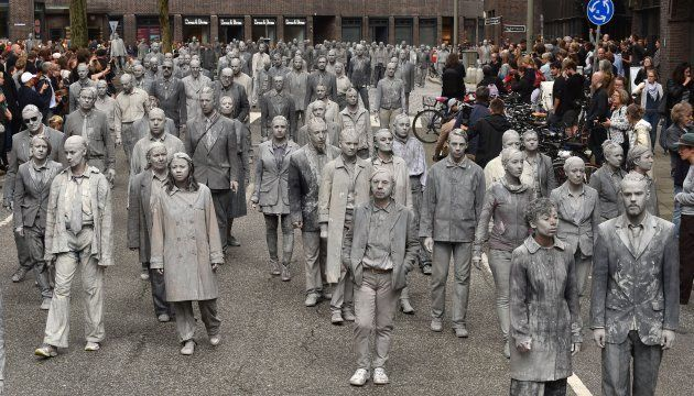 Performers smeared with clay demonstrate during the art