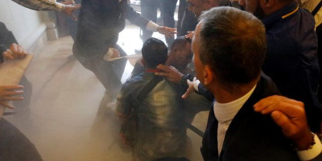 People attack a government supporter after he and a group of fellow government supporters burst into...