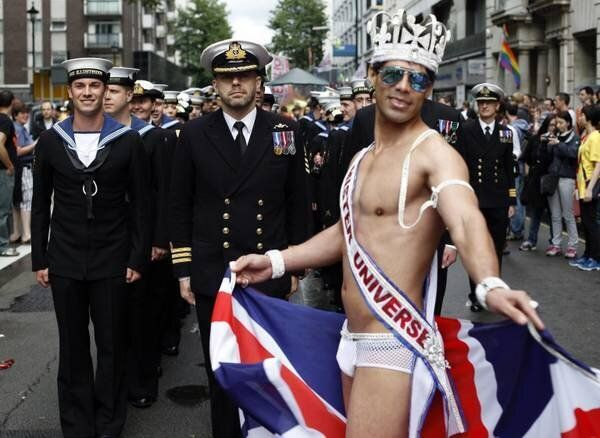 epa03298912 Members of the Royal Navy march behins a costumed participant during the annual Gay Pride...