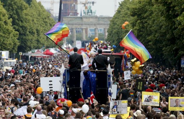 People participate in the annual Christopher Street Day parade in front of the Brandenburg Gate in Berlin,...