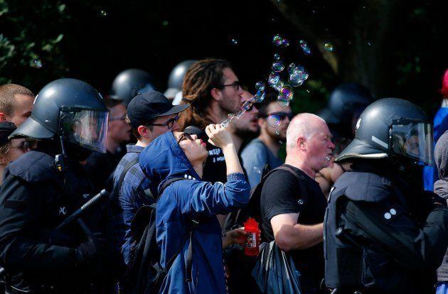 Una ragazza protesta contro il G20 Amburgo spargendo bolle di sapone e diventa un