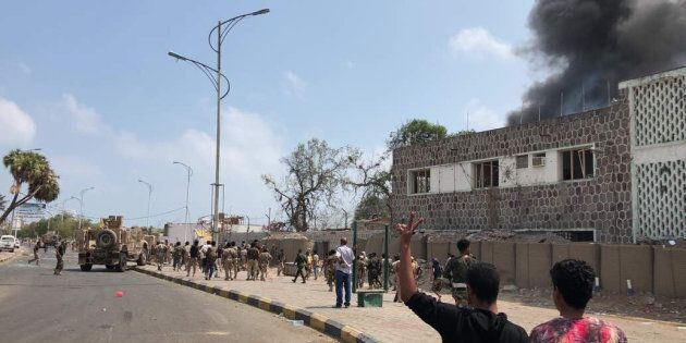 Yemeni men and security forces inspect the site of a suicide bombing in the southern port city of Aden,...
