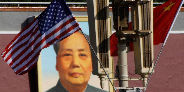 U.S. and China's flags flutter in front of a portrait of late Chinese Chairman Mao Zedong at the Tiananmen...