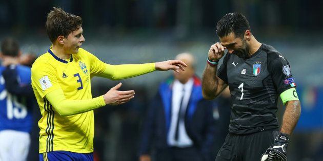 Victor Lindelof of Sweden comforting Gianluigi Buffon of Italy at the end of the match at San Siro Stadium...