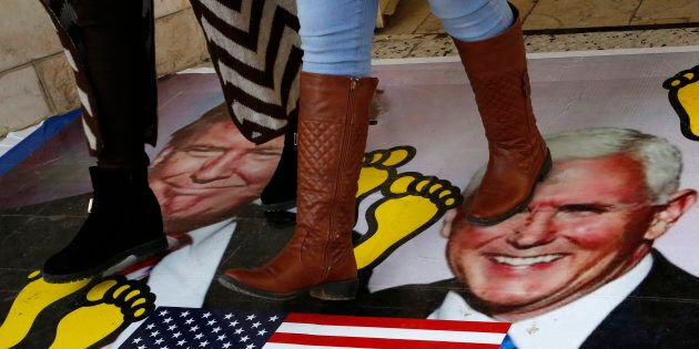 Palestinians walk on a poster bearing images of US President Donald Trump (L) and his deputy Mike Pence...