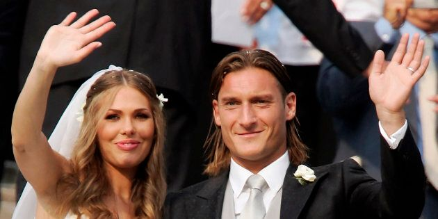 The captain of Italian Serie A football club AS Roma, Francesco Totti (R), waves after his wedding to...