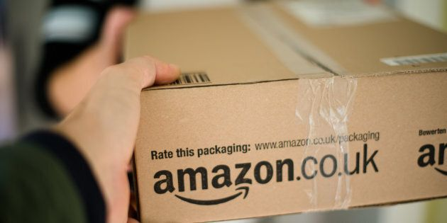 Stuttgart, Germany - September 23, 2012: Woman receiving a parcel by Amazon.com delivered by the mailman...