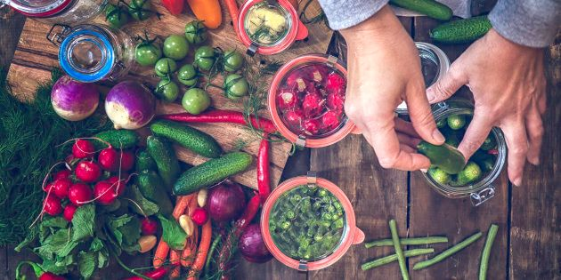 Preserving organic vegetables in jars like carrots, cucumbers, tomatoes, chilis, paprika and