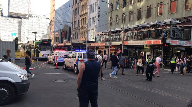 Pedestrians walk past as police and emergency services attend the scene of an incident involving a vehicle...