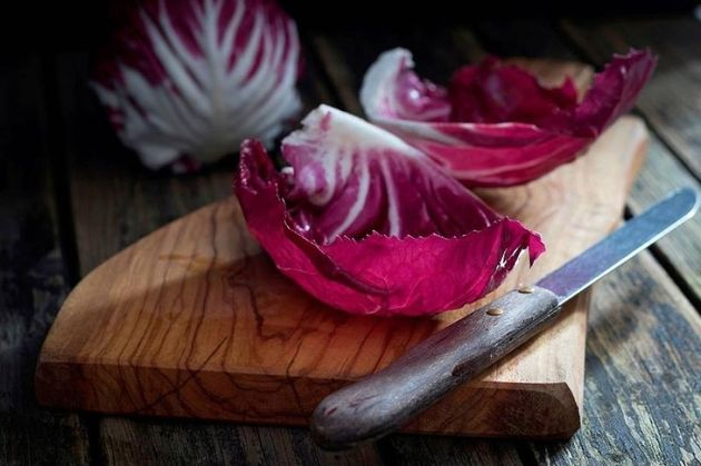 Leaves of radicchio and kitchen knife on wooden