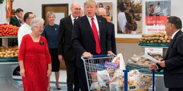 US President Donald Trump pushes a shopping cart as he tours the Church of Jesus Christ of Latter-Day...
