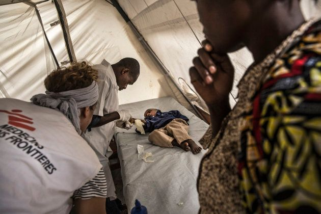A mother watches her child, who she just brought to the CTC in Katana is examined by MSF nurses for cholera