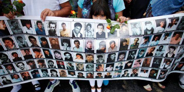 Una bambina tiene uno striscione con tutte le persone uccise nel 1995 nel massacro di