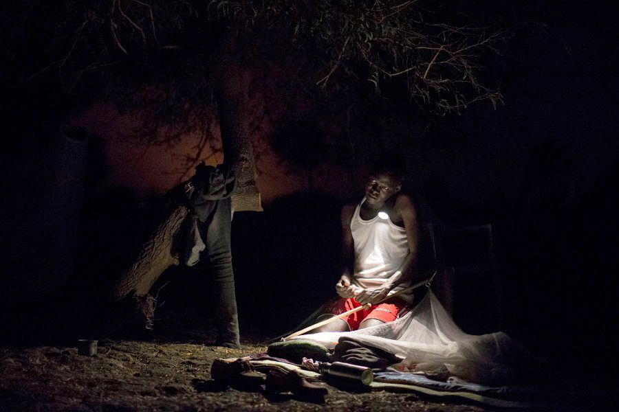 James*, a Medecins Sans Frontieres (MSF) Community Area Supervisor organises his bedding for the night...