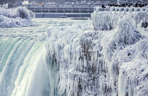 Visitors take photographs at the brink of the Horseshoe Falls in Niagara Falls, Ontario, as cold weather...