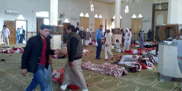 Egyptians walk past bodies following a gun and bombing attack at the Rawda mosque, roughly 40 kilometres...