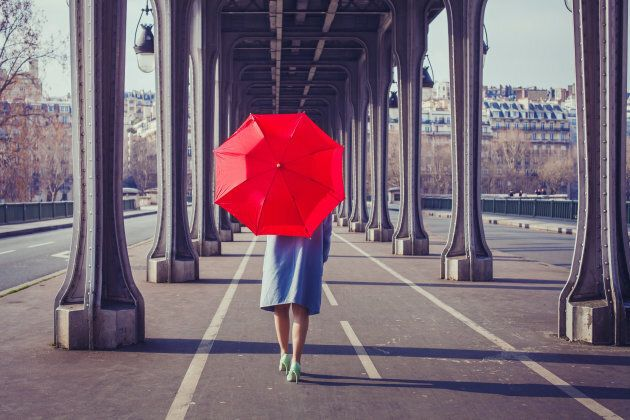 fashion woman with red umbrella walking on the street in