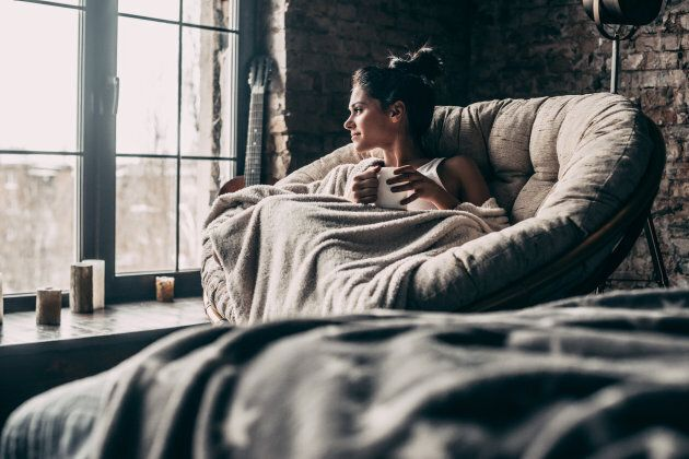 Attractive young woman covered with blanket looking through window and holding a cup while sitting in...