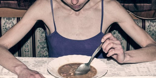 Anorexia. Skinny anorexic girl holding a spoon and look at the plate with