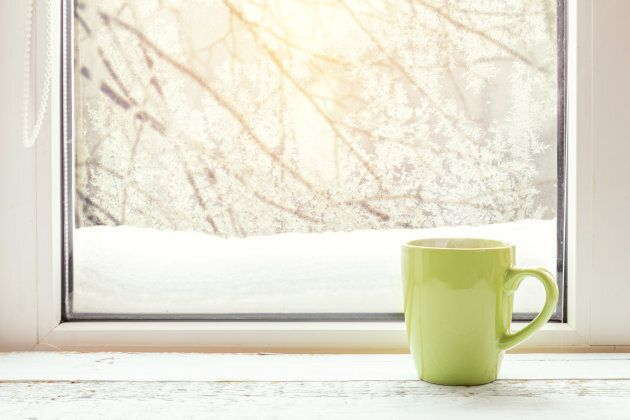 Cup of coffee on the window sill. In the background frosty pattern on window as a Christmas background...