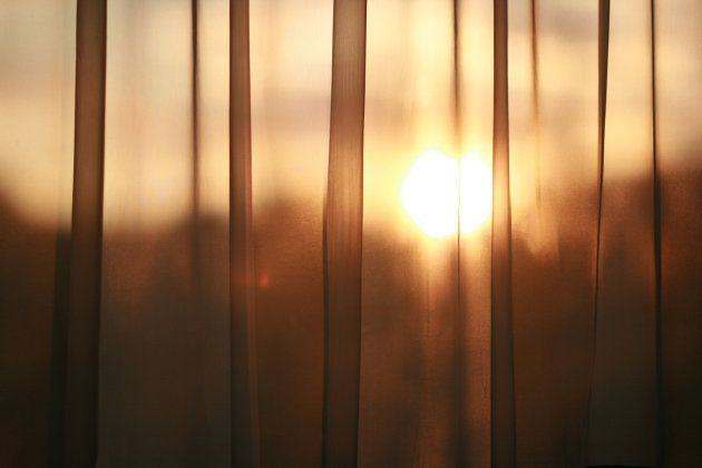 Golden sun (sunset) shining through curtain. Look out the window at the golden sunset through