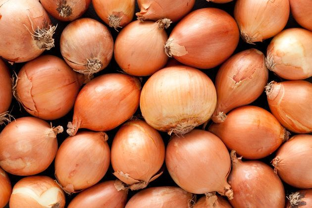 A top view of a layer of yellow onions. The onions have brown skins. They are arranged randomly. The...