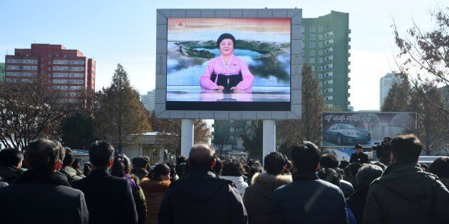 Pyongyang residents watch a big screen near the Pyongyang Railway Station showing the news on the successful...