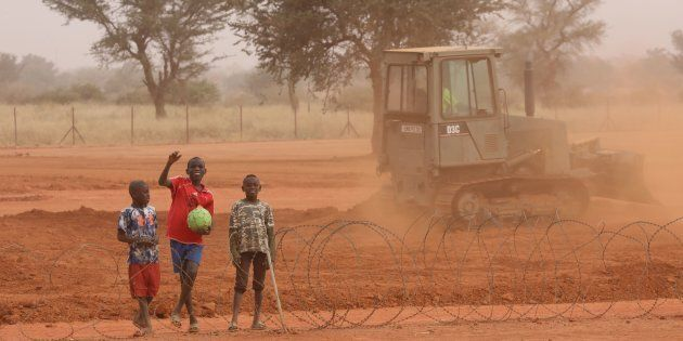 Nigerien children walk and play along the fences of the Barkhane French air force base on December 23,...
