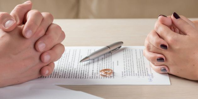 hands of wife and husband signing divorce documents or premarital