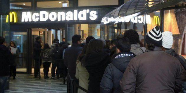 Alcune persone in coda al McDonald's in Galleria Vittorio Emanuele, Milano, 2 dicembre 2013. ANSA/MATTEO