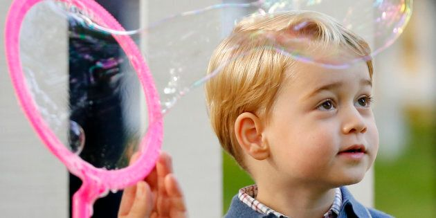 Britain's Prince George watches as bubbles are blown at a children's party at Government House in Victoria,...