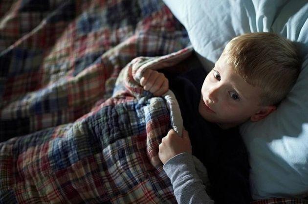 a boy laying awake in