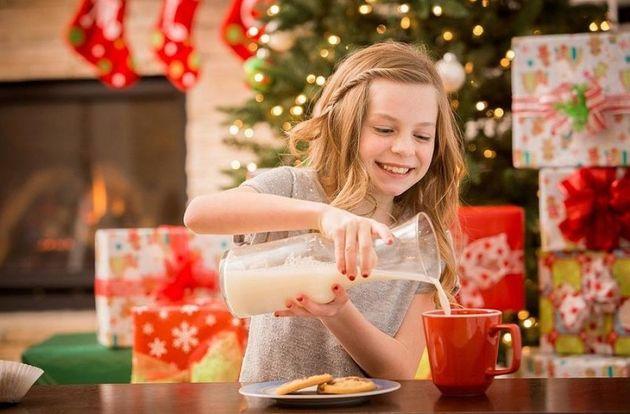 Caucasian girl leaving cookies and milk for Santa at