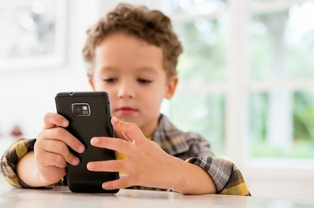 Four year old boy playing games on a cell