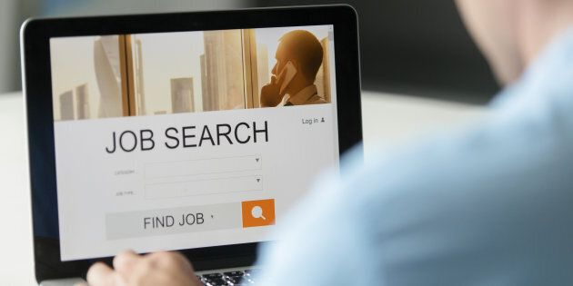 Monitor view over a male shoulder, job search title on the screen, close up. Education, business concept