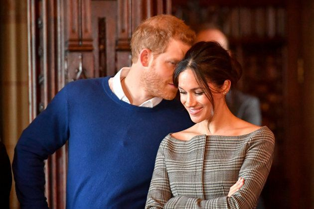 Britain's Prince Harry whispers to Meghan Markle as they watch a performance by a Welsh choir in the...