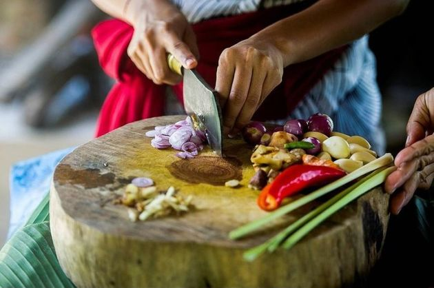 Close up of chefs chopping vegetables on cutting