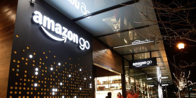 Amazon employees are pictured outside the Amazon Go brick-and-mortar grocery store without lines or checkout...