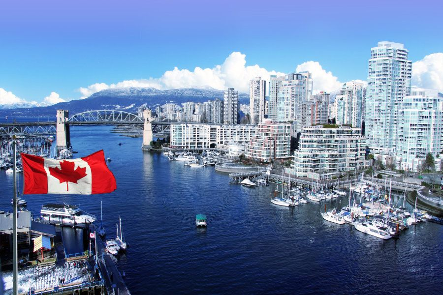 Canadian flag in front of view of False Creek and the Burrard street bridge in Vancouver,
