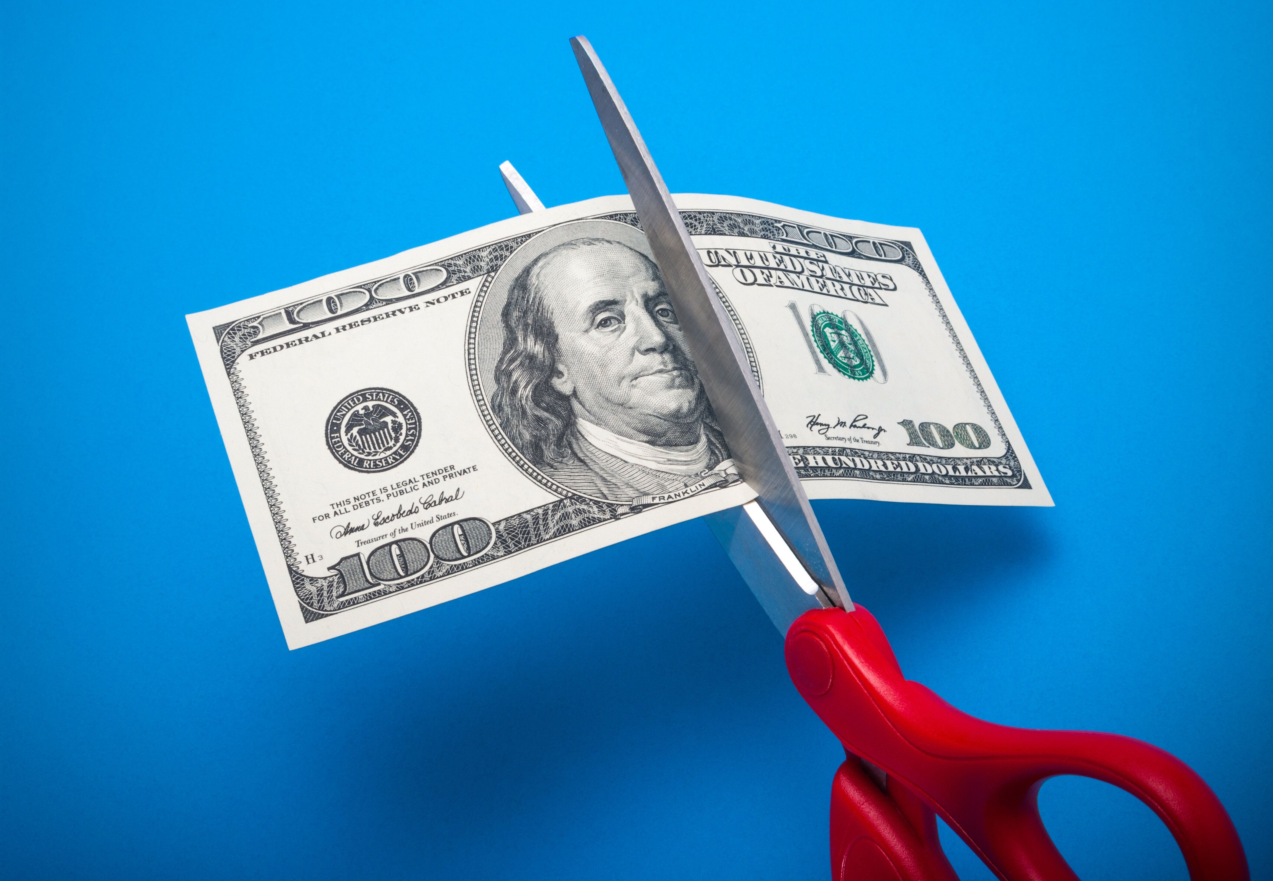 100 dollar bill being cut with scissors isolated on a blue background