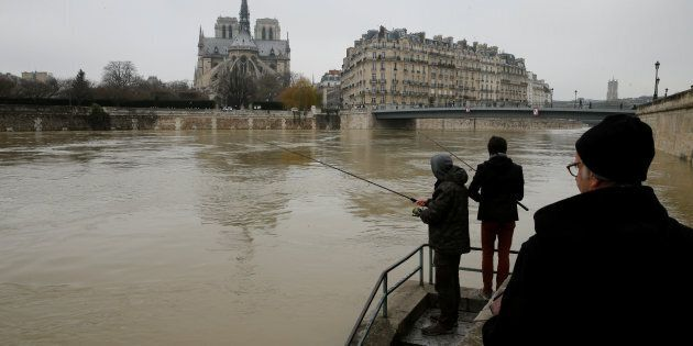 Two men fish on the flooded banks of the River Seine in Paris, France, after days of almost non-stop...