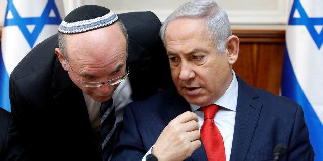 An advisor speaks to Israeli Prime Minister Benjamin Netanyahu at the beginning of the weekly cabinet...