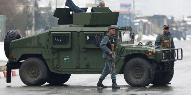 Afghan policemen keep watch near the site of an attack at the Marshal Fahim military academy in Kabul,...
