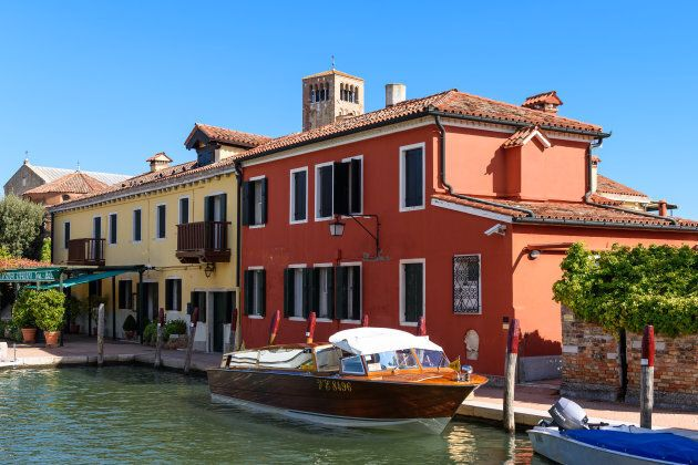 Torcello: Water taxi parked in front of colorful buildings alongside of the main canal of Torcello island,...