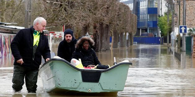 Municipal employees assist a resident who sits in a boat as the Marne River overflows its banks in Gournay-sur-Marne,...
