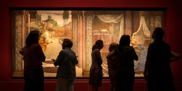 Museum workers stand in front of a fresco by Italian renaissance painter Sandro Botticelli