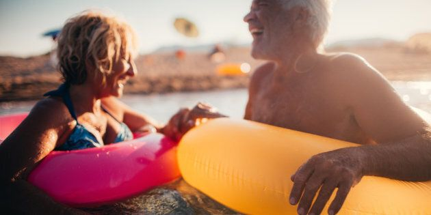 Photo of a cute, smiling senior couple being goofy while bathing in the sea with a swimming tubes. Wide...