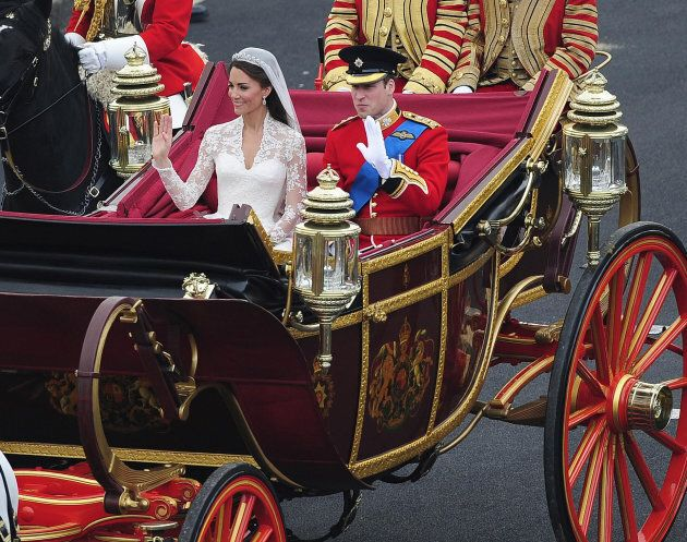 Prince William and his bride Kate proceed around Parliament Square and into Whitehall in an open topped...