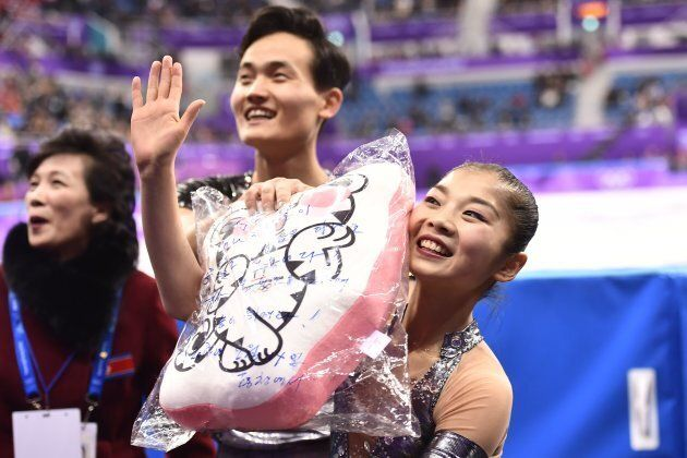 North Korea's Ryom Tae Ok (R) and North Korea's Kim Ju Sik react after competing in the pair skating...